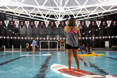 A person stands on a paddleboard in a pool